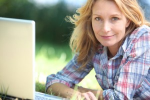 Woman using laptop computer in the park